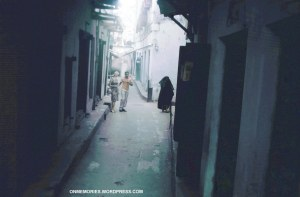 Dick-Dick and Shannon Moeser in Zanzibar street, near woman in burka, July 5, 1964.